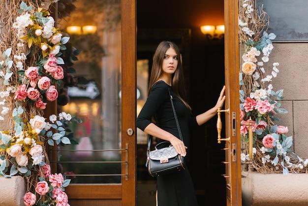 Stylowa elegancka piękna młoda dziewczyna w czarnej sukience otwiera drewniane drzwi do restauracji