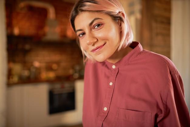 Stylowa fajna nastolatka bez makijażu, różowawej fryzury bob i pierścienia w nosie pozuje w pomieszczeniu