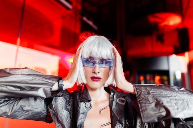 Stylowa futurystyczna blondynka w stylu cyberpunk na czerwonym lustrze.