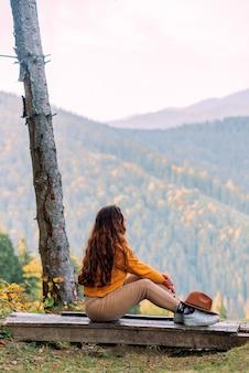 Stylowa hipster dziewczyna siedzi w lesie szczęśliwa kobieta ciesząca się jesienną naturą piękny krajobraz koncepcja podróży stylem życia żółty sweter żółte liście na drzewach widok z górskiego wzgórza