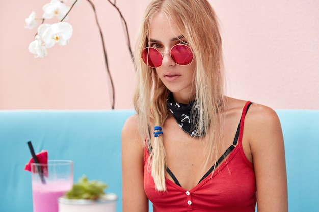 Stylowa hipster kobieta w czerwonych modnych okularach przeciwsłonecznych, siedzi na niebieskiej wygodnej kanapie