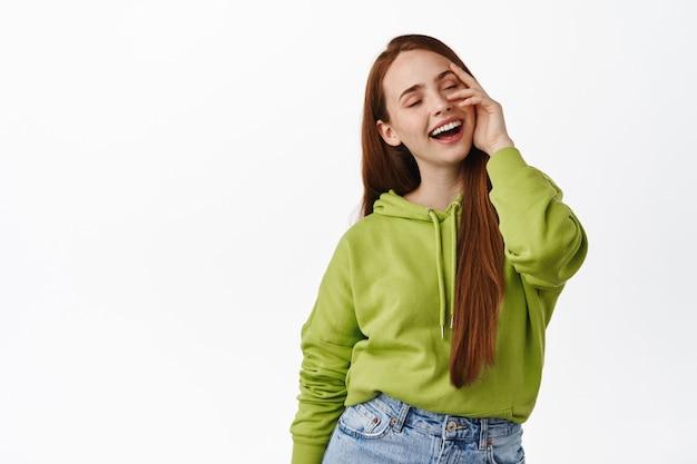 Stylowa i beztroska rudowłosa naturalna dziewczyna, śmiejąca się i uśmiechnięta beztrosko, dotykająca lśniącej, czystej skóry, stojąca szczęśliwa na białym