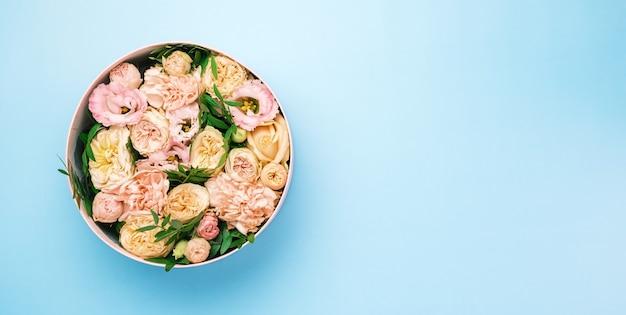 Stylowa i delikatna kompozycja kwiatowa w okrągłym pudełku kapeluszowym na różowym tle z miejscem na kopię. pudełko prezentowe na 8 marca, międzynarodowy dzień kobiet, dzień matki, walentynki, urodziny,