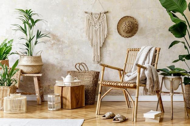Stylowa i kwiatowa kompozycja wnętrza salonu z rattanowym fotelem, mnóstwem tropikalnych roślin w designerskich donicach, dekoracją, makramą i eleganckimi dodatkami osobistymi w przytulnym wystroju domu.