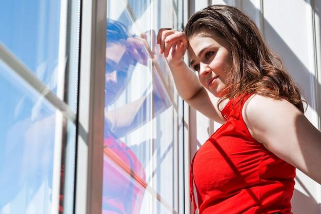 Stylowa i piękna biznesowa kobieta w czerwonej bluzce wygląda przez okno. za oknem słoneczna pogoda, cień z okna pada na dziewczynę.