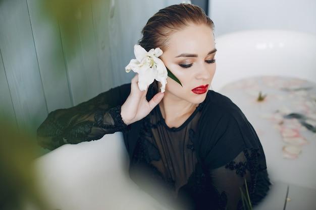 Stylowa i piękna dziewczyna leży w łazience