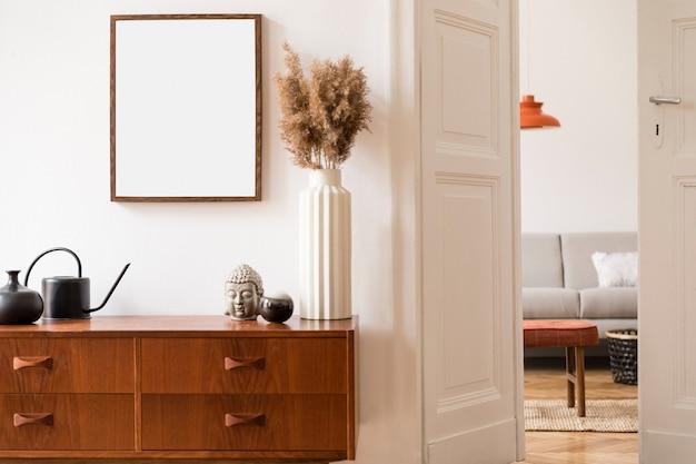 Stylowa i retro przestrzeń wnętrza domu z makiety ramki plakatowej, szafka vintage z akcesoriami retro, suszone kwiaty w wazonie, rośliny. neutralny wystrój domu. szablon.
