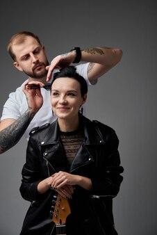 Stylowa i seksowna para punk na ciemnym tle studia w skórzanych kurtkach w tatuażach dziewczyna ma czerwone okulary