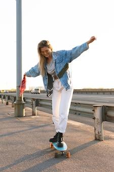 Stylowa i szczęśliwa dziewczyna próbuje jeździć na longboardzie