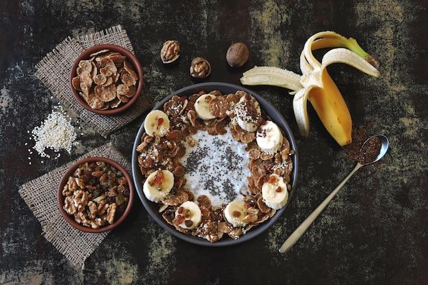 Stylowa i zdrowa miska śniadaniowa. flat lay. zdrowe śniadanie z jogurtem, nasionami chia, płatkami, bananem.