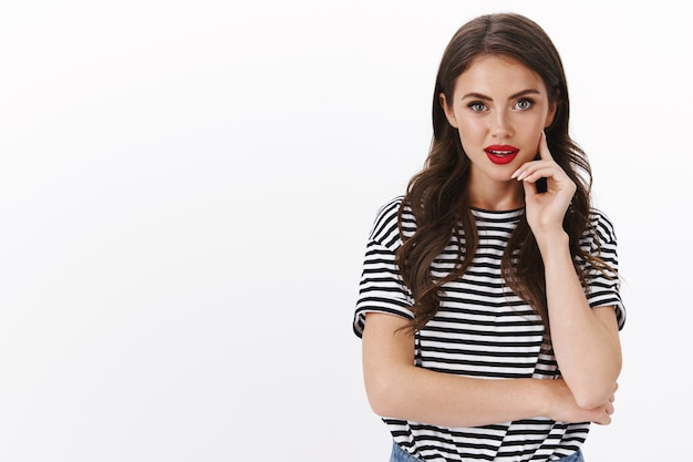 Stylowa, intrygująca, nowoczesna kaukaska kobieta nosi czerwoną szminkę, pasiasty t-shirt, słuchanie rad członków zespołu, zarządzanie biznesem, dotyk, policzek, zamyślony, zastanawia się nad wyborami