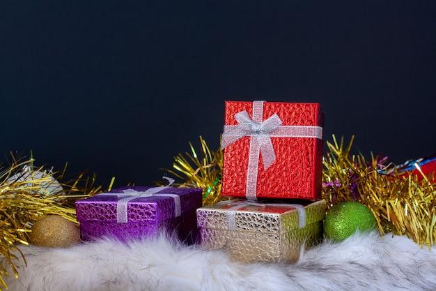 Stylowa kartka świąteczna z kolorowymi pudełkami na prezenty, bombkami i świątecznym blichtrem. skopiuj miejsce na górze na ciemnym tle.