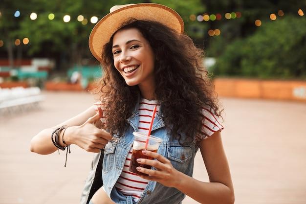 Stylowa kaukaska kobieta z kręconymi brązowymi włosami, pije napój z plastikowego kubka, odpoczywając w hipsterskim miejscu lub nowoczesnym parku z kolorowymi lampami