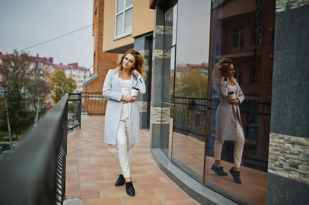 Stylowa kędzierzawa blondynka modela dziewczyny odzież na bielu z filiżanką kawy pod ręką pozuje przeciw dużemu okno.
