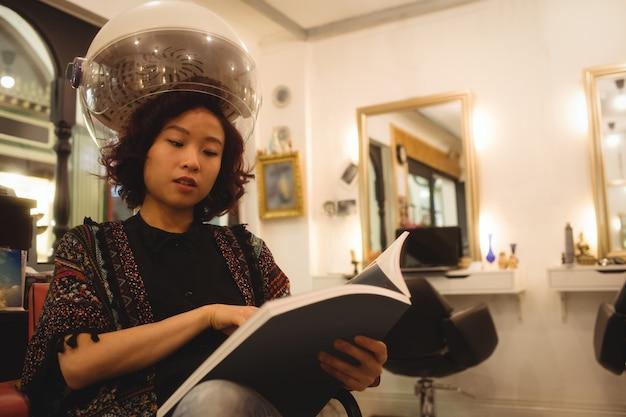 Stylowa kobieta czyta czasopismo siedząc pod suszarką do włosów