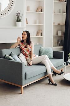 Stylowa kobieta gryzie prawoślazu na kanapie. codzienna odzież i szpilki siedząc na nowoczesnej kanapie z poduszkami i gryząc pyszną piankę.