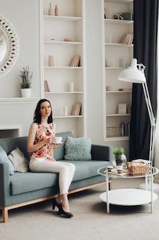 Stylowa kobieta gryzienie ptasie mleczko na kanapie. codzienna odzież i obcasy siedzące na nowoczesnej kanapie z poduszkami i gryzące pyszne pianki.