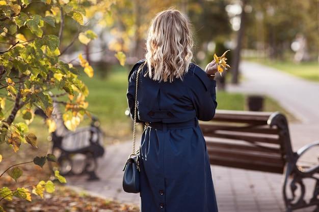 Stylowa kobieta idzie w parku jesień.