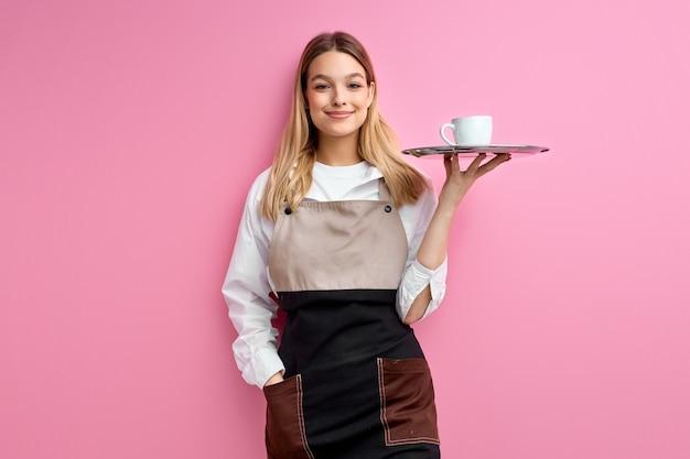 Stylowa kobieta kelnerka w fartuchu, oferując filiżankę pysznej, smacznej kawy