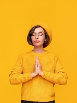 Stylowa kobieta medytuje z założonymi rękami