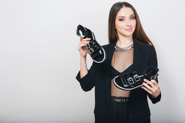 Stylowa kobieta na białym tle w czarnym garniturze trzymając pait butów