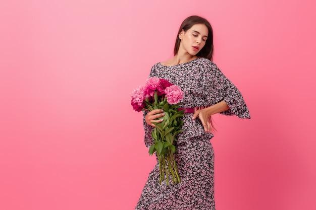 Stylowa kobieta na różowo w modnej letniej sukience z bukietem kwiatów piwonii