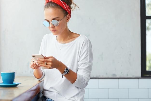 Stylowa kobieta noszenie chustka siedzi w kawiarni