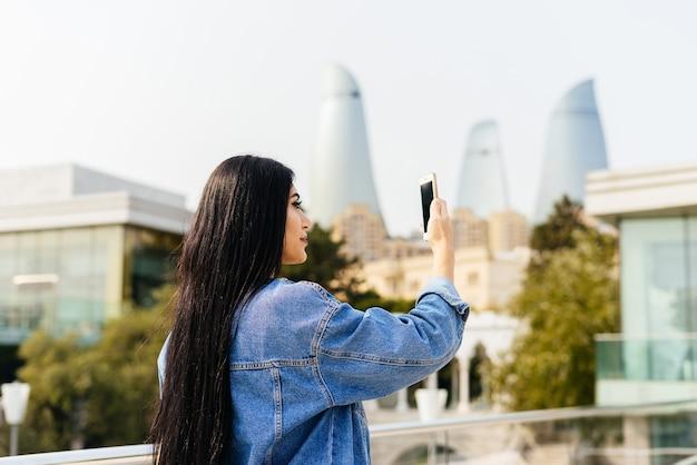 Stylowa kobieta patrząca na telefon na tle miasta