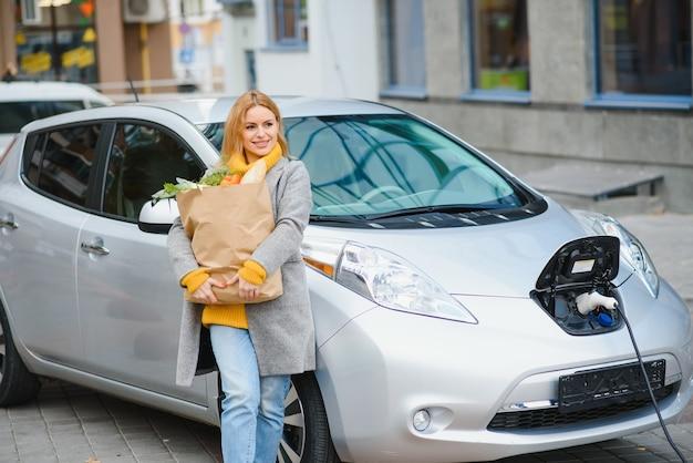 Stylowa kobieta po zakupie produktów z torbą na zakupy stoi w pobliżu ładującego się samochodu elektrycznego