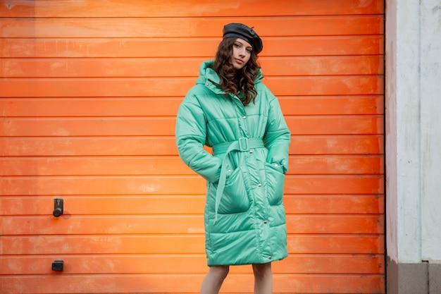 Stylowa kobieta pozuje zimą jesień trend w modzie puchowy płaszcz i kapelusz beret na pomarańczowej ścianie na ulicy