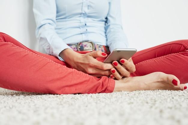 Stylowa kobieta siedzi na podłodze ze smartfonem