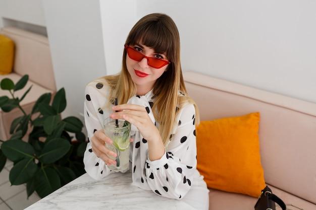 Stylowa kobieta siedzi w kawiarni i picia koktajli