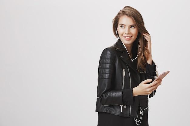 Stylowa kobieta skręca w lewo, uśmiechnięta, słuchająca muzyki i korzystająca z telefonu komórkowego
