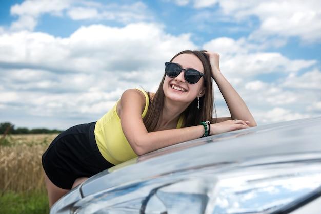 Stylowa kobieta stojąca w pobliżu swojego samochodu i ciesząca się wolnością na łonie natury poza miastem