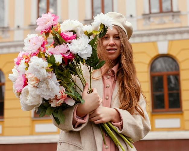 Stylowa kobieta trzyma bukiet kwiatów na zewnątrz na wiosnę