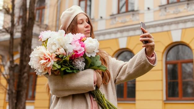 Stylowa kobieta trzyma bukiet kwiatów na zewnątrz wiosną i przy selfie