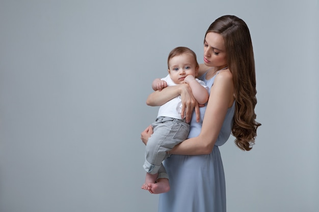 Stylowa kobieta trzymająca małe dziecko na białym tle na niebieskim tle piękna matka i syn rasy kaukaskiej