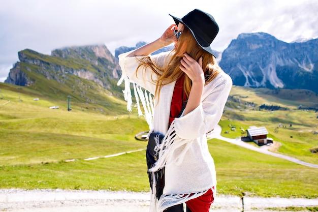 Stylowa kobieta ubrana w elegancki luksusowy strój w stylu boho, pozuje w niesamowitych dolomitach