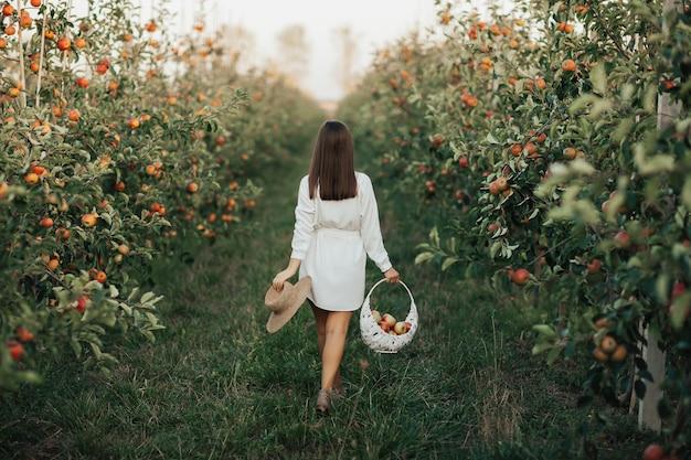 Stylowa kobieta w białej sukni w letnim sadzie.