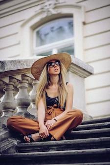 Stylowa kobieta w białym kapeluszu siedzi na schodach