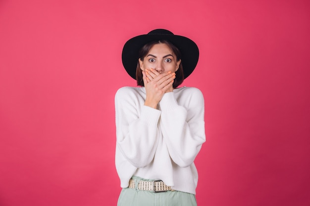 Stylowa kobieta w białym swetrze i kapeluszu na czerwono różowej ścianie