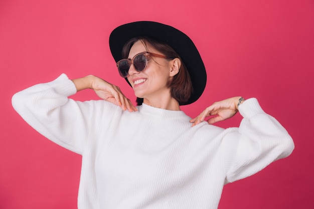 Stylowa kobieta w białym swetrze, okularach przeciwsłonecznych i kapeluszu na czerwonej różowej ścianie