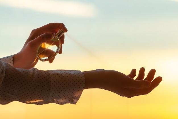 Stylowa kobieta w bluzce stosowania perfum na jej nadgarstku o zachodzie słońca