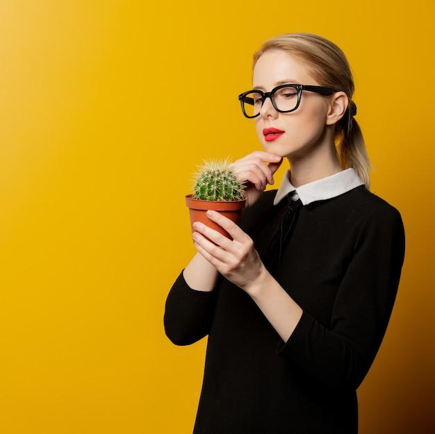 Stylowa kobieta w czarnych formalnych ubraniach z kaktusem