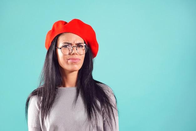 Stylowa kobieta w czerwonym berecie zmarszczyła brwi na aparat