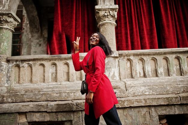 Stylowa kobieta w czerwonym płaszczu postawiona na starych kolumnach i pokazuje dwa palce znak