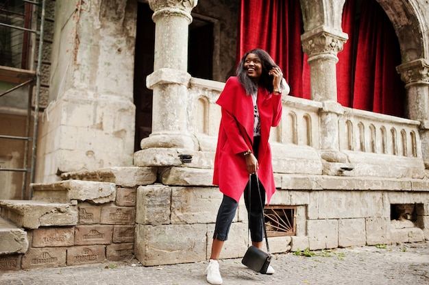 Stylowa kobieta w czerwonym płaszczu postawiona na starych kolumnach