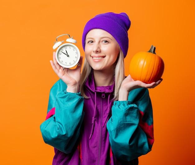 Stylowa kobieta w dresie z lat 90. z dynią i pomarańczowym budzikiem