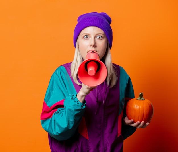 Stylowa kobieta w dresie z lat 90. z dynią i pomarańczowym megafonem