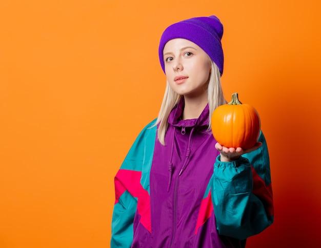 Stylowa kobieta w dresie z lat 90. z dynią na pomarańczowo